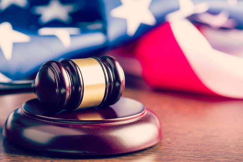 A gavel rests in front of an American Flag in a courtroom