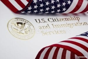 American Flags flank A US Citizenship and Immigration Services sign