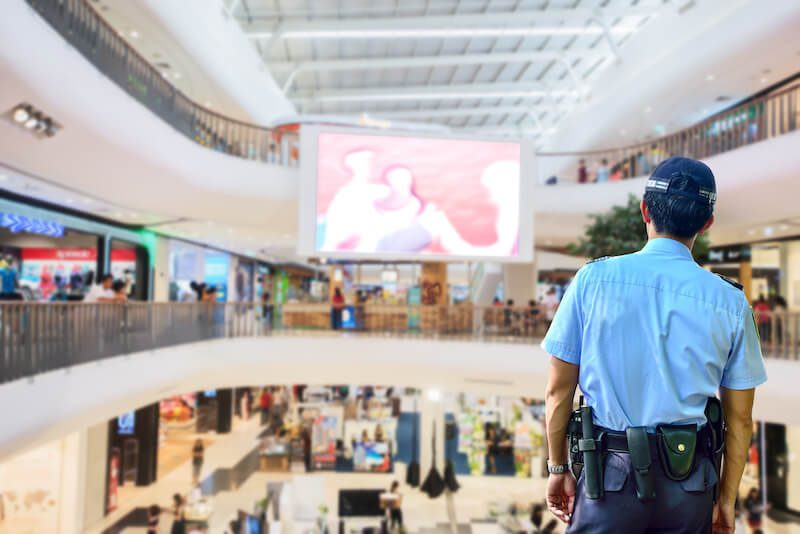 A security guard stands at a vantage point to view three levels at a mall