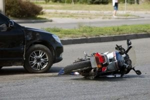 After an accident a motorcycle lies in the street next to a damaged car