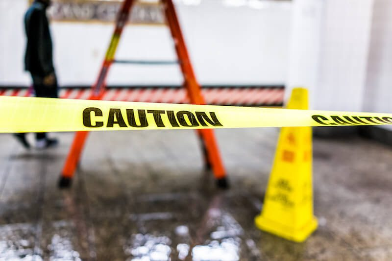 Caution tape blocks a hazardous area at a business