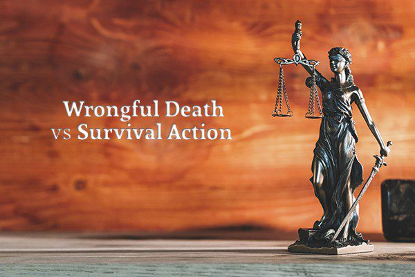 "A small statue of ""blind justice"" sits on a desk beside the words ""Wrongful Death vs Survival Action"""