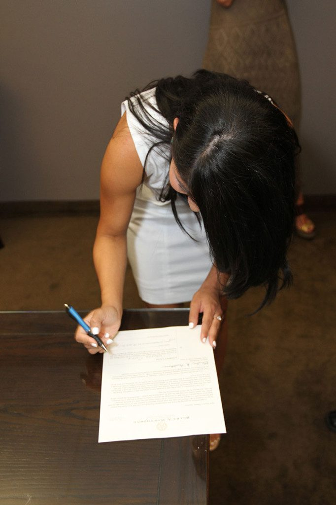 Cassandra Garcia signing a document