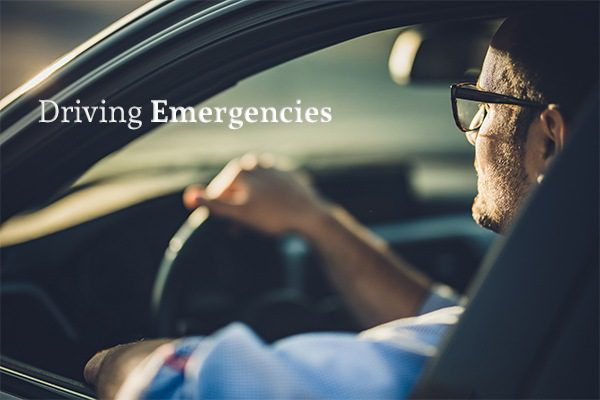 "A man sitting in a car driving beside the words ""Driving Emergencies"""
