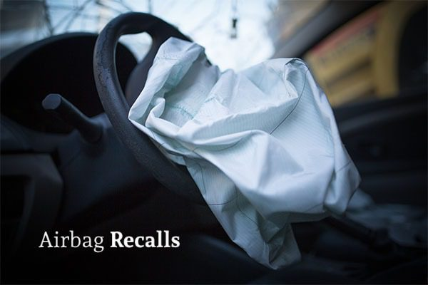 A deflated front driver airbag in a car with the words airbag recalls