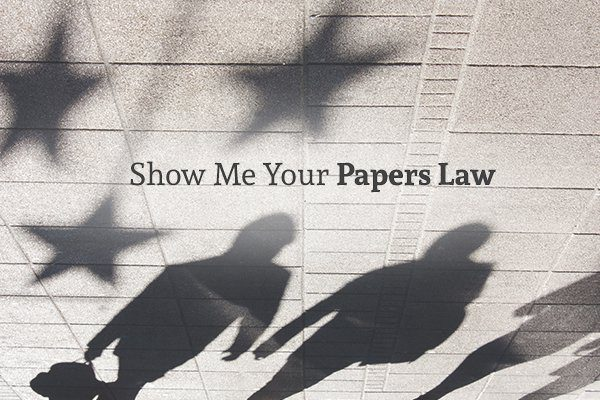 A walkway showing the shadows of four people, the shadows of three stars, and the words show me your papers law