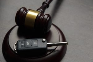 A gavel is sitting on a desk with a car key.