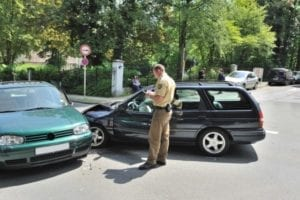 A police officer is writing a report on a parking lot accident.