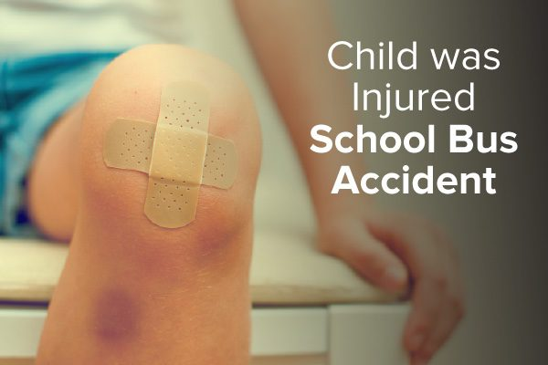 A child sitting on an examination table with a band-aid on his knee with words that say, child was injured school bus accident.