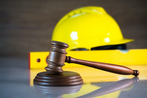 A gavel in front of a hard hat and a level.