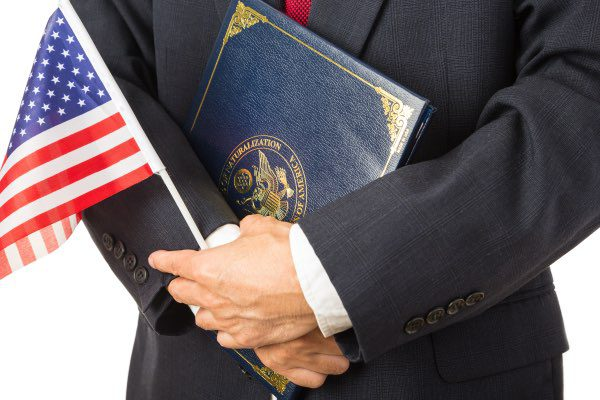 A man is holding an American flag and a new citizenship packet.