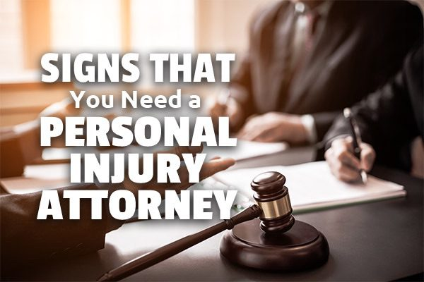 Lawyers meeting with a client with the words, signs that you need a personal injury attorney.