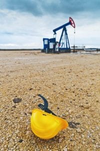 A safety helmet in front of an oilfield