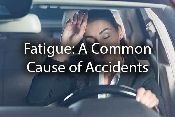 "A lady is tired while driving with the words, ""Fatigue: a common cause of accidents."""