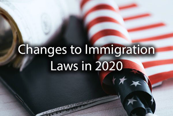 "A rolled up American Flag along with some documents that says, ""changes to immigration laws in 2020."""