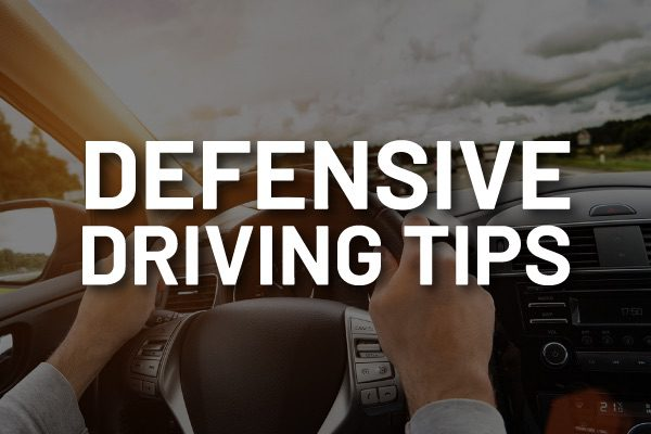 "A person driving with the words, ""defensive driving tips."""