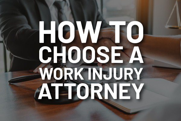 """An attorney going over paper work with the words, """"how to choose a work injury attorney."""""""