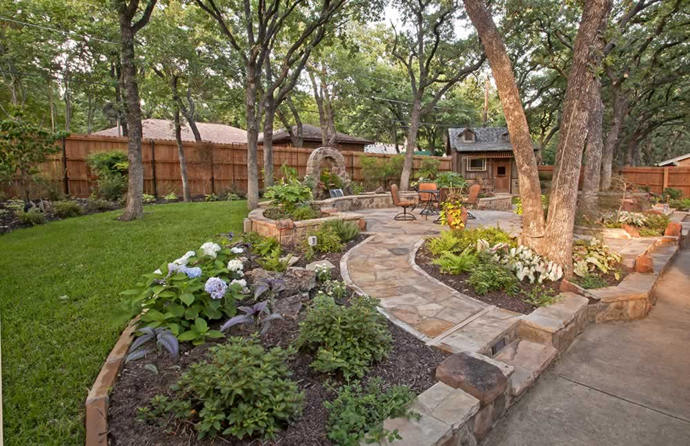 Surronded by landscaping a stone patio contains a relaxing sitting area