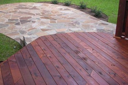 A wooden deck with a stone patio attached