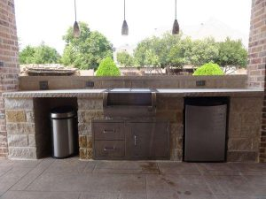 Outdoor kitchen made of brick and stones with lighting fixtures