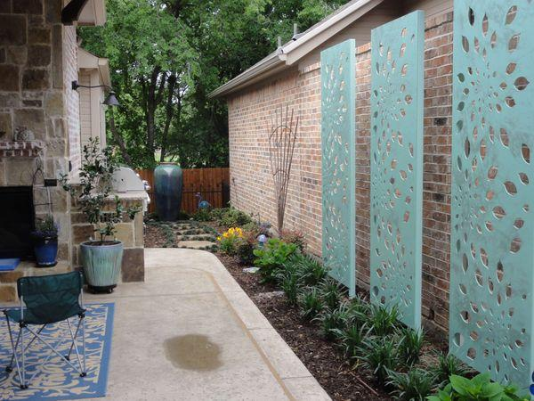 Backyard patio alley surrounded by beautiful landscaping and sculptures
