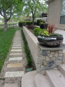 Stone pathway next to a rock retaining wall and black flower pot