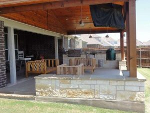 Beautiful custom made back patio with wood ceiling and raised stone walls