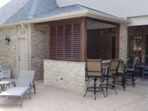 Wooden shutters hiding a outdoor kitchen and stone decking