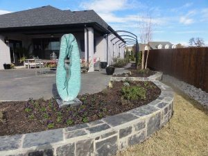 cool stone flower bed with yard art