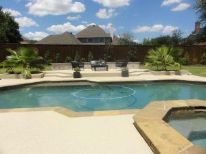 Backyard pool with stone coping and concrete decking