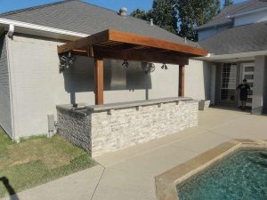 Outdoor bar made of thin cut stones and wooden pergola