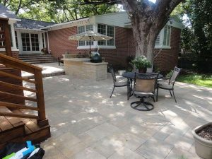 Backyard patio made of stone with a wooden covered deck