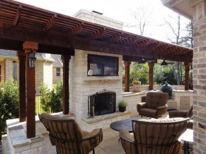 Back yard seating around a TV and fireplace with wooden pergola