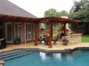 Wooden pergola covering an outdoor kitchen and fire place