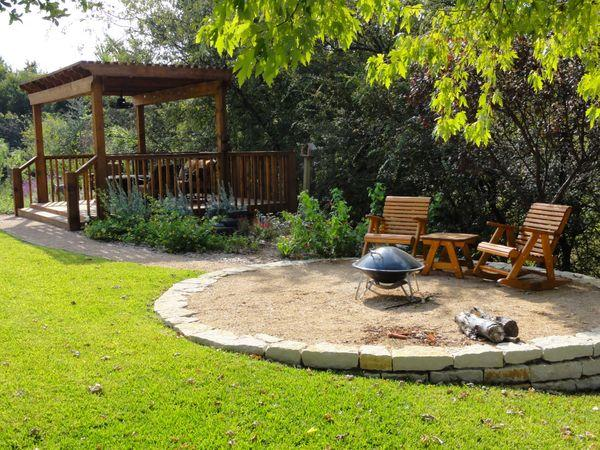 Outdoor seating area around a fire pit on a raised stone platform