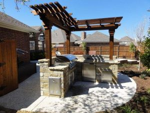 Outdoor kitchen design made of stone and wooden pergola