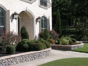 front view of a home with rock retaining walls holding landscaping