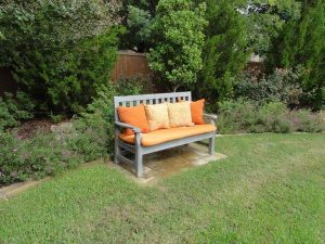Wooden bench with orange cushions