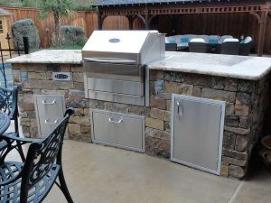 Outdoor kitchen with grill and fridge