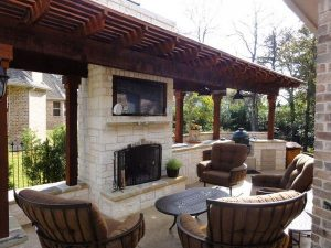 Outdoor seating around a tv and custom fire place