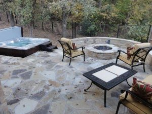 Backyard patio made of stone with a jacuzzi