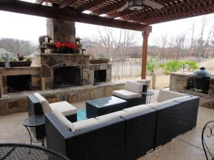 Outdoor seating under a wooden pergola and fire places