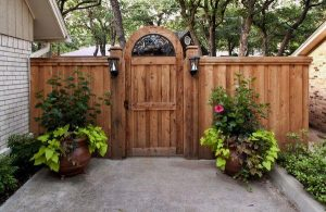 Wooden fence with lighting fixtures and plants in pots