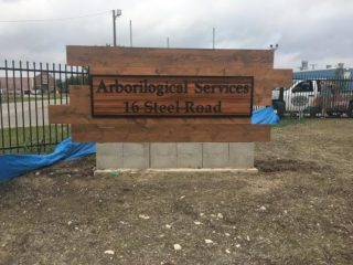Wooden storefront sign for Arborilogical Services