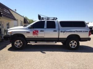Silver work truck with decals for search and recovery company
