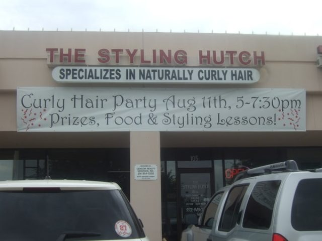 Hair salon with banner hanging that advertises a Curly Hair Party