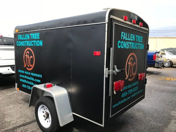 Black enclosed trailer with blue decals for tree construction company
