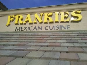 Yellow and black storefront sign for Frankies Mexican Cuisine
