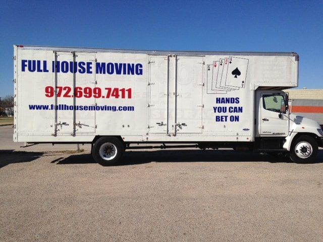 White moving truck with red and blue vinyl decals for moving company