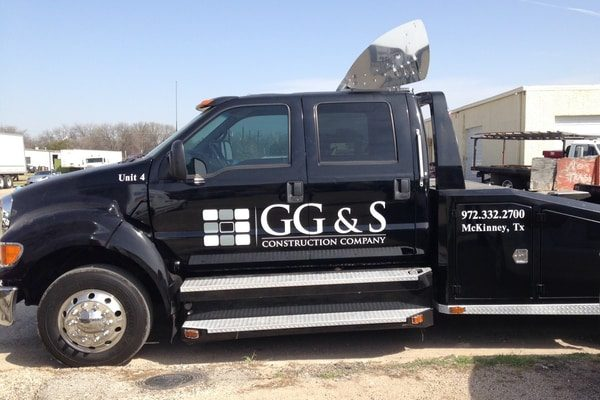 Black work truck with white vinyl decals for construction company